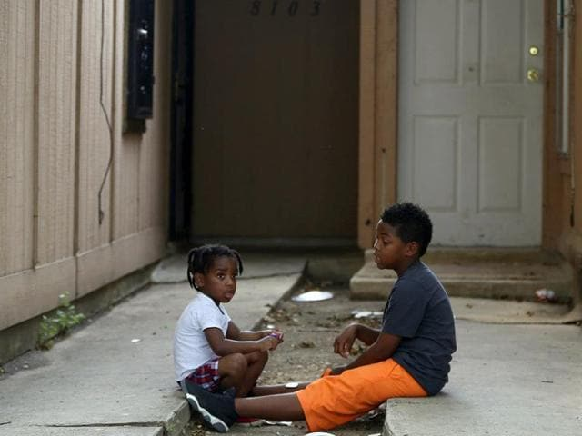 Kids play Friday April 29, 2016 in front of the townhouse in San Antonio, Texas, where children were allegedly chained up in the back yard.
