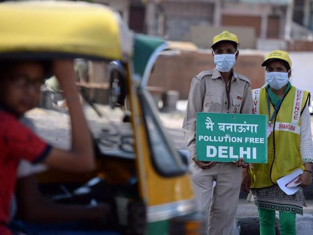 Civil defence volunteers stand with placards to promote the odd-even scheme at a traffic junction in New Delhi.