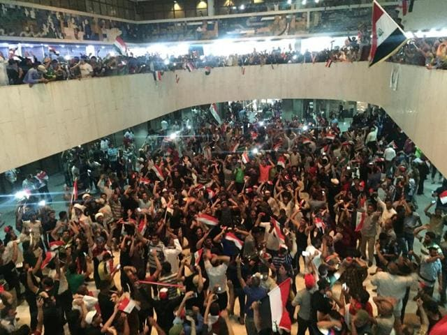Followers of Iraq's Shia cleric Moqtada al-Sadr are seen at the parliament building as they storm Baghdad's Green Zone after lawmakers failed to convene for a vote on overhauling the government on Saturday.