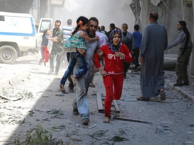 Syrians evacuate an injured man amid the rubble of destroyed buildings following a reported air strike on the rebel-held neighbourhood of Al-Qatarji in Aleppo.