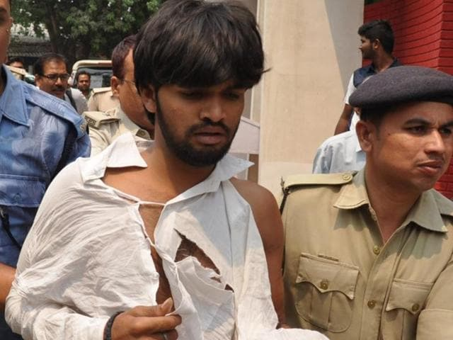 One of the two men who waved black flags at  Kanhaiya Kumar in Patna being detained by police after he was beaten up by the JNU students' union president's supporters.