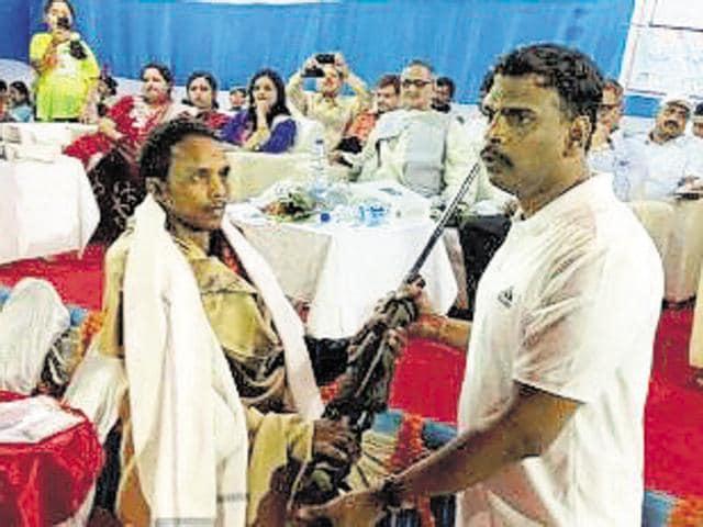 Lohardaga SP Karthik S (right) presents a shawl to Maoist area commander Sarvesh Ganjhu, who surrendered on Saturday, and takes his gun in return.