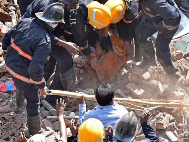 The crowd gather near a building that collapsed at Kamathipura in Mumbai on Saturday.