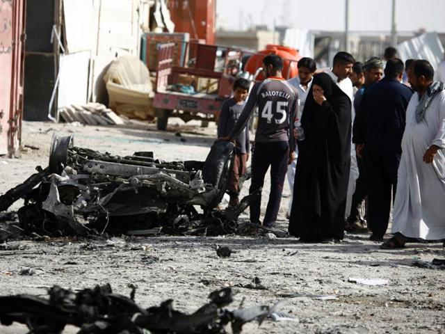 Iraqis react as they look at the damage following a twin suicide bombing attack in the southern Iraqi city of Samawah.