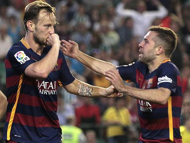 Barcelona's Ivan Rakitic, left, celebrates with teammate Jordi Alba, right, after scoring against Betis.