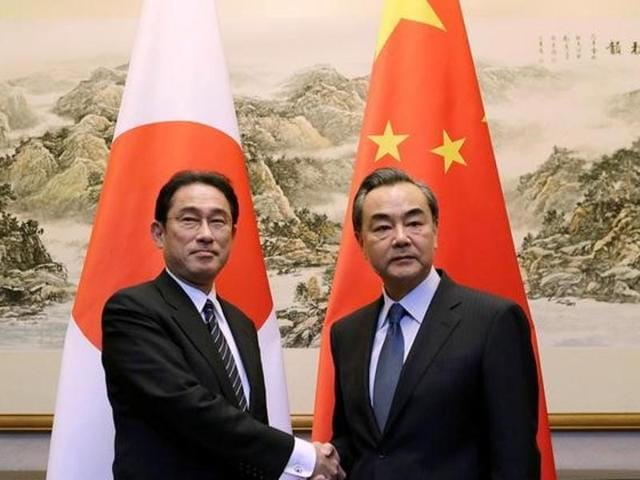 Japanese foreign minister Fumio Kishida shakes hands with China's foreign minister Wang Yi during a meeting at Diaoyutai State Guesthouse, in Beijing, China.