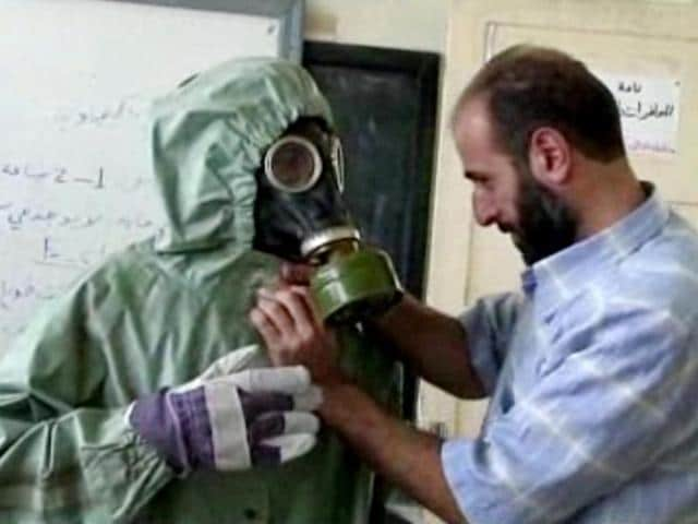 This image made from an AP video shows a volunteer adjusting a students gas mask and protective suit during a session on reacting to a chemical weapons attack in Aleppo.