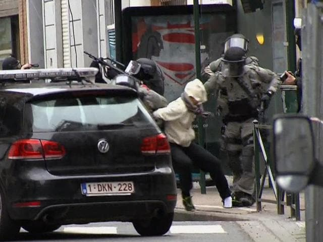 In this Friday March 18, 2016 file framegrab taken from VTM, Salah Abdeslam, centre, is arrested by police and bundled into a police vehicle during a raid in the Molenbeek neighborhood of Brussels, Belgium.