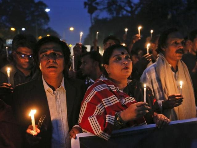 In this file photo, Bangladeshi people hold lighted candles and walk in a rally during Martyrs Day in Dhaka, Bangladesh.