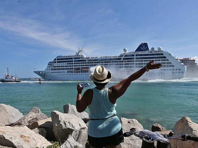A woman from Cuba waves at Adonia las the cruise leaves the port in Miami, en route to Cuba.