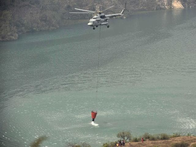 An IAF helicopter carrying water to spray on a forest fire in Uttarakhand.