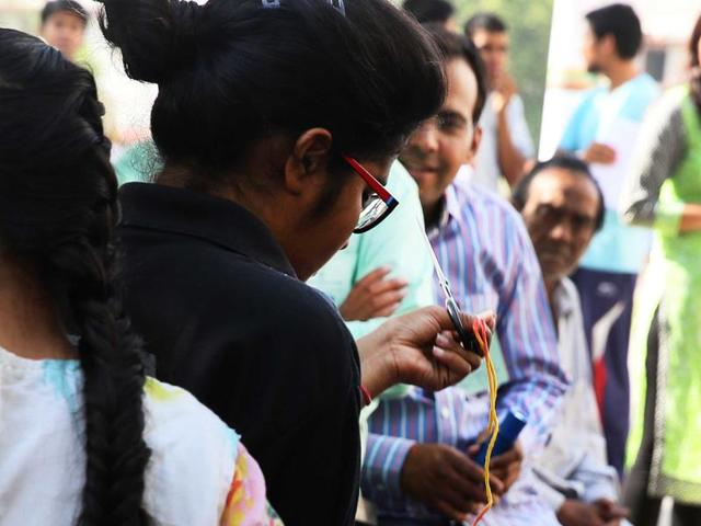 A candidate appearing in the National Eligibility cum Entrance Test  takes off sacred thread tied on her wrist as per official instructions, prior to entering the examination center in Jaipur, Rajasthan on Sunday.