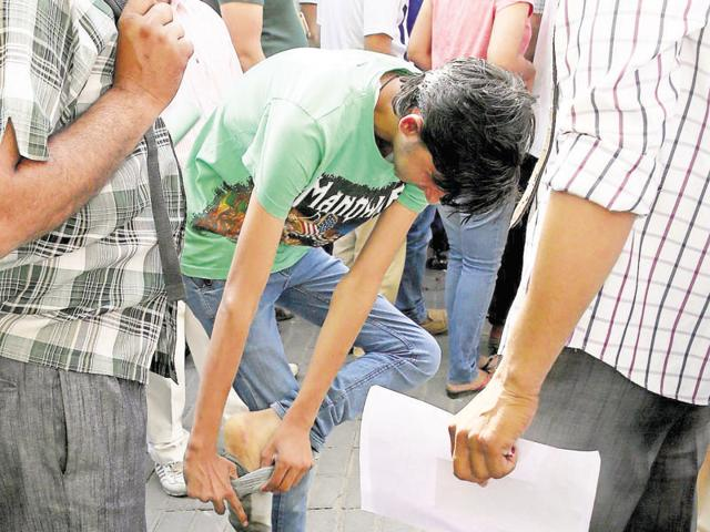 A National Eligibility Entrance Test aspirant takes off his shoes and socks before entering an examination centre in Jaipur on Sunday.