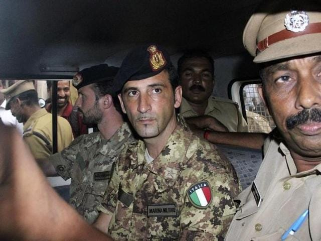 Salvatore Girone (centre L) and Latorre Massimiliano (3rd R), members of the navy security team of Napoli registered Italian merchant vessel Enrica Lexie, sit in a police vehicle.