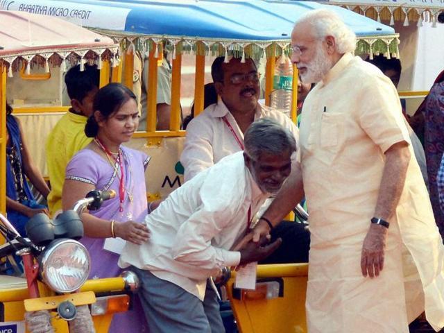 Prime Minister Narendra Modi interacting with the e-rickshaw beneficiary, in Varanasi, Uttar Pradesh on Sunday.