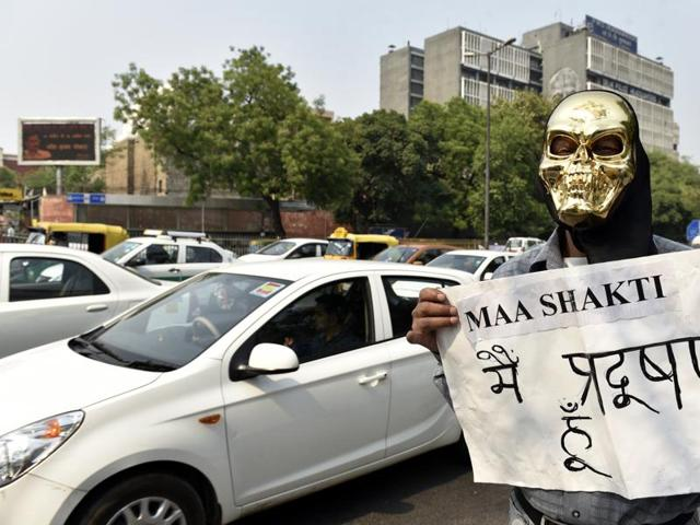 A social worker dressed up as 'pollution' holds a banner during the odd-even traffic plan in Delhi.