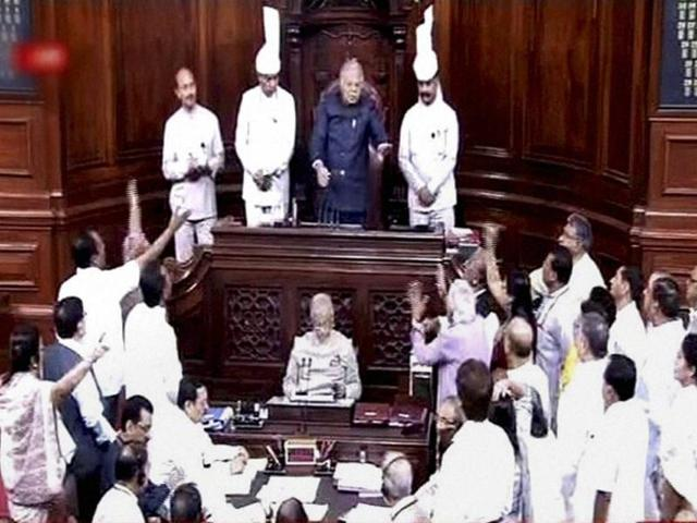 Members protest in the well of the Rajya Sabha in New Delhi on Monday.