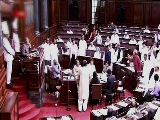 Members protest in the well of the Rajya Sabha
