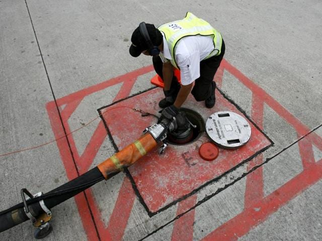 A technician attaches a jet fuel supply pipe to an outlet in the tarmac at an airport. Aviation Turbine Fuel (ATF) or jet fuel prices were hiked by 1.5%.