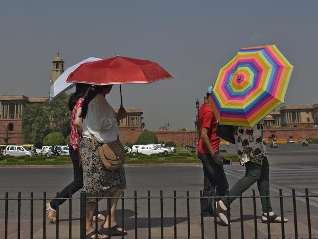 Tourists shield themselves as they visit Vijay Chowk in Delhi's heart.