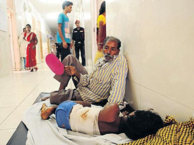 Dinkar Oraon and his 10-year-old daughter in the corridor of the RIMS burns ward.