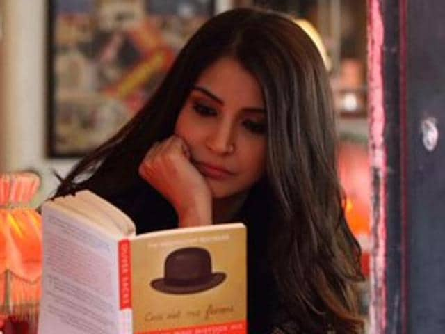 Filmmaker Karan Johar has shared a picture that shows Anushka Sharma reading The Man Who Mistook His Wife For A Hat by Oliver Sacks in what appears to be a cafe.(Twitter)