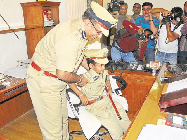Girish Sharma dressed as police commissioner is helped by Commissioner Srinivas Rao Janga  to sit on his chair.