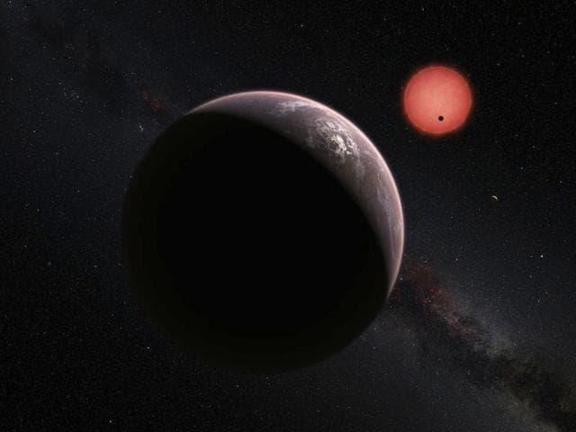 This artist's impression shows an imagined view of the three planets orbiting an ultracool dwarf star just 40 light-years from Earth.