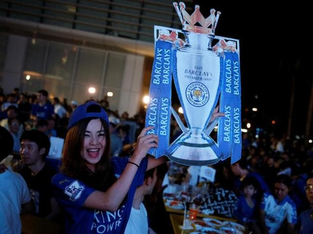 Leicester City fans celebrate after their team drew against Manchester United.