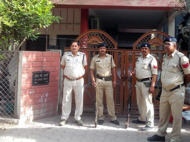 Cops stand guard outside the house of sub-engineer Rajendra Sharma during Lokayukta search in Indore on Tuesday.
