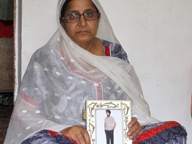 The mother of Inderpal Ahuja holding his photograph at her home in Ludhiana.