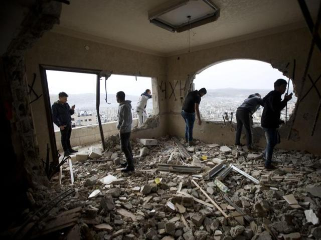 Palestinians inspect the damaged house of Zaid Amer, after it was demolished by the Israeli army, in the West Bank city of Nablus, Tuesday, May 3, 2016.