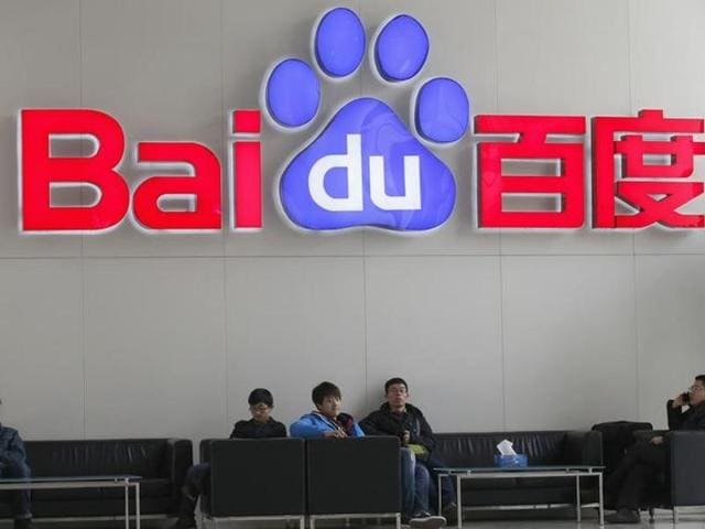 A woman walks past the Baidu booth at the China International Technology Fair in Shanghai.