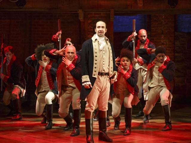 This image released by The Public Theatre shows Lin-Manuel Miranda, foreground, with the cast during a performance of Hamilton, in New York.
