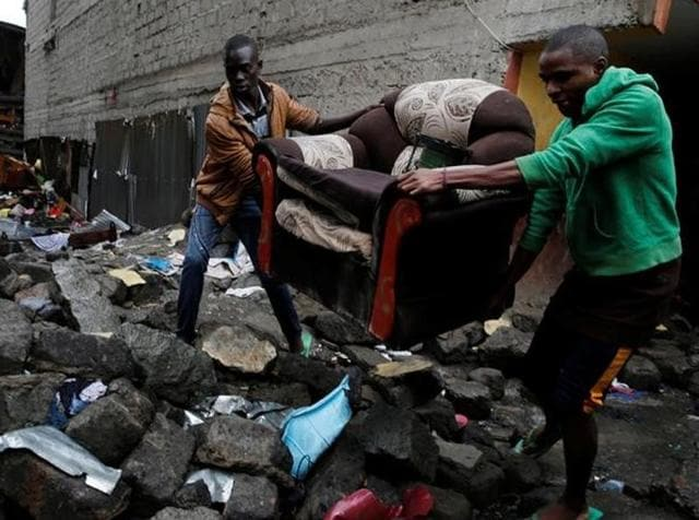 People carry a sofa as they leave the Huruma neighbourhood during the search for residents feared trapped in the rubble of a six-storey building that collapsed after days of heavy rain, in Nairobi.