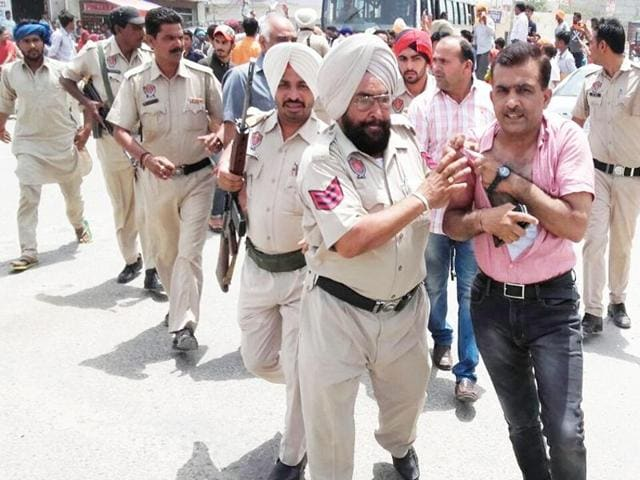 Sanjeev Trikha, private secretary of senior Congress leader Sunil Jakhar, being taken to a police station in Abohar on Tuesday.