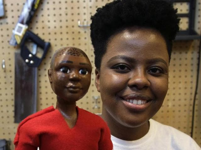 Jennifer Pierre of Fort Lauderdale, a student at Babson College, holds her prototype doll named Jaylen in a workroom at the school, in Wellesley, Mass.