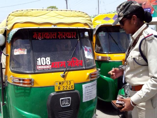 A policewoman inspects an auto at Simhastha area.