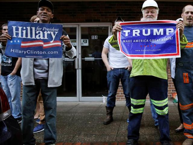 Supporters of US Democratic presidential candidate Hillary Clinton and Republican presidential Donald Trump cheer outside a campaign event in Williamson, West Virginia.