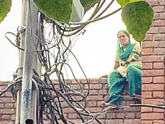 Woman sitting on the roof of a CRPF flat after a dispute with her husband at Dugri in Ludhiana on Wednesday.