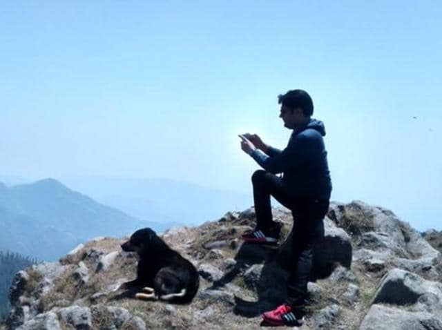 In a picture posted by him on Twitter on Wednesday, he is seen taking pictures of the stunning view from a hill and with him is a dog, seemingly appreciating the scenery itself.