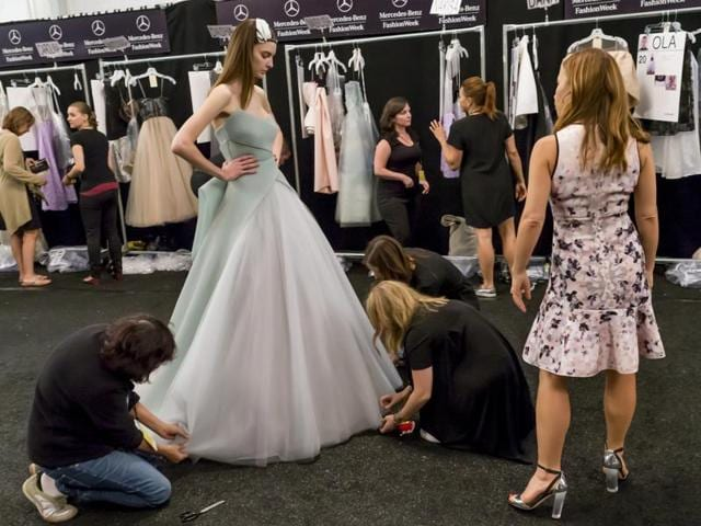 A representative photo of a model being dressed for  a fashion show