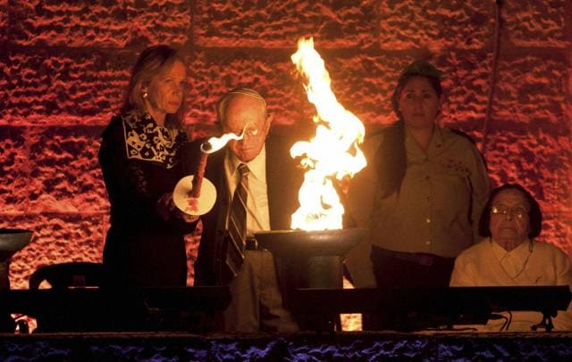 Holocaust survivor Robert Tomashof and his daughter Rutti Tomashof light a torch during the opening ceremony of the Holocaust Remembrance Day at the Yad Vashem Holocaust Memorial in Jerusalem on Wednesday.