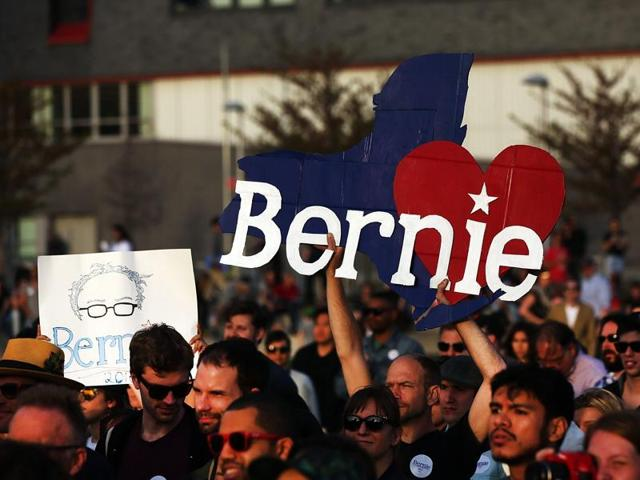People cheer as Democratic presidential candidate Bernie Sanders walks on stage at a campaign rally in New York City.