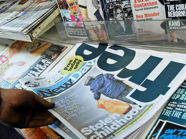 A customer holds a copy of The New Day at a newsagents in London on February 29, the day it was launched.