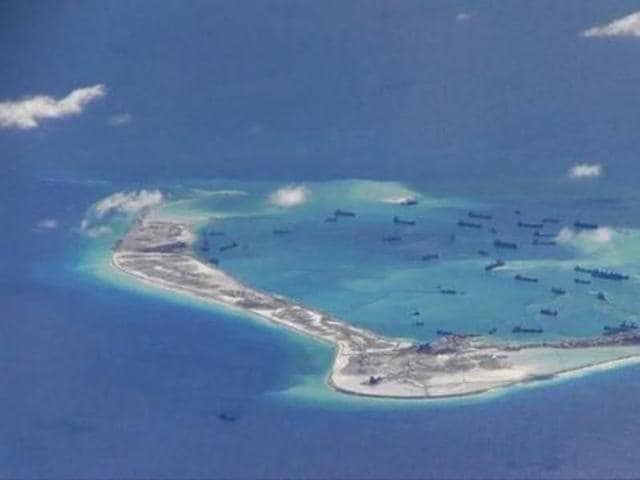 Chinese dredging vessels are purportedly seen in the waters around Mischief Reef in the disputed Spratly Islands in the South China Sea in this still image from video taken by a P-8A Poseidon surveillance aircraft provided by the United States Navy in 2015.