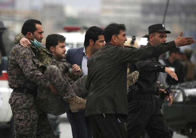 Afghan security forces carry an injured security personnel after a suicide car bomb attack in Kabul, Afghanistan.
