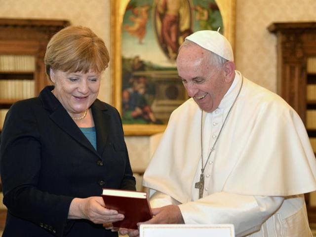 German Chancellor Angela Merkel (left) shakes hands with Pope Francis during a private audience at the Vatican on Friday. Merkel is in Rome to take part in a ceremony for awarding Germany's famed Charlemagne Prize to the pope.