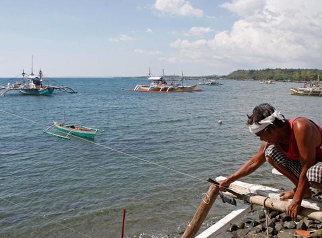 A fisherman repairs his boat overlooking fishing boats that fish in the disputed Scarborough Shoal in the South China Sea, at Masinloc, Zambales, in the Philippines April 22, 2015.