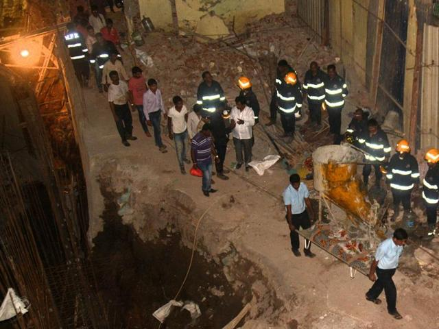 Rescue workers carry the body of one of the labourers killed after an under-construction wall caved in; Rescue operations lasted seven hours.